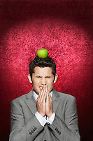 Man cringing with apple on head against red velvet background