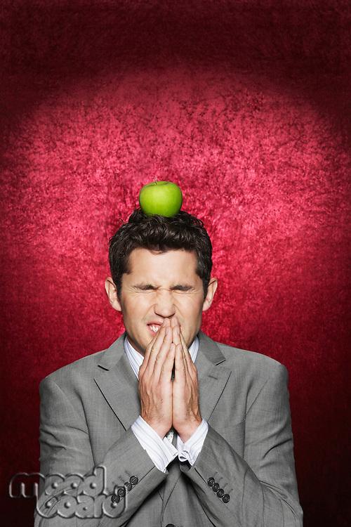 Man cringing with apple on head against red velvet background