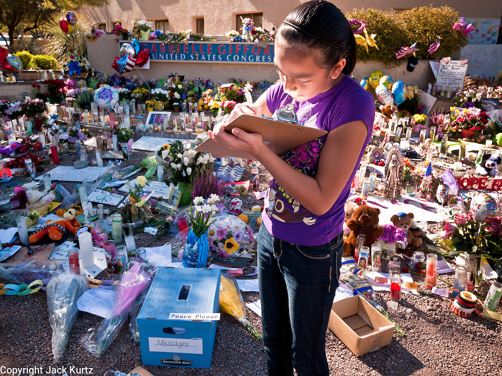 """15 JANUARY 2010 - TUCSON, AZ:    ALYSIA SIMMONS writes a note for Congresswoman Gabrielle Giffords at a memorial in front of the Congresswoman's office in Tucson, AZ, Saturday, January 15. Six people were killed and 14 injured in the shooting spree at a """"Congress on Your Corner"""" event hosted by Arizona Congresswoman Gabrielle Giffords at a Safeway grocery store in north Tucson on January 8. Congresswoman Giffords, the intended target of the attack, was shot in the head and seriously injured in the attack but is recovering. Doctors announced that they removed her breathing tube Saturday, one week after the attack. The alleged gunman, Jared Lee Loughner, was wrestled to the ground by bystanders when he stopped shooting to reload the Glock 19 semi-automatic pistol. Loughner is currently in federal custody at a medium security prison near Phoenix.    PHOTO BY JACK KURTZ"""