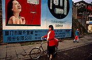 Chinese citizens walk beneath a billboard for shower and bathroom equipment in the new megacity of Shenzhen, China. A happy-looking woman showers herself with a big smile on her face and Chinese characters give more details below. A smart-looking lady walks her bicycle past, a matching red suitcase strapped at the back.