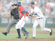 Mississippi's Errol Robinson (6) is tagged out by Virginia's Branden Cogswell (7) on a botched hit and run in the College World Series in Omaha, Neb. on Sunday, June 15, 2014. Virginia won 2-1.