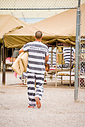 "17 JULY 2006 - PHOENIX, AZ: An inmate carries his bedding across the yard before the National Anthem was played in ""Tent City"" in the Maricopa County Jail in Phoenix, AZ. There are about 650 inmates living in the tents. Maricopa County Sheriff Joe Arpaio recently started playing the Star Spangled Banner and God Bless America twice a day in the county jails. Inmates are encouraged, but not forced, to stand at attention with their hands over their hearts, when the music is played. When asked about the new policy Arpaio said, ""Our men and women are fighting and dying for our country in Iraq and that's the least these inmates can do."" In 2011, the US Department of Justice issued a report highly critical of the Maricopa County Sheriff's Department and the jails. The DOJ said the Sheriff's Dept. engages in widespread discrimination against Latinos during traffic stops and immigration enforcement, violates the rights of Spanish speaking prisoners in the jails and retaliates against the Sheriff's political opponents.      PHOTO BY JACK KURTZ"