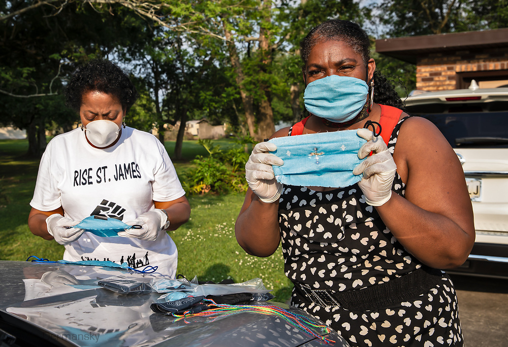 Stephanie Cooper, the Vice presdient of RISE St. James, right, and Sharon Lavigne, left, with masks Cooper made. Cooper shows off a mask with a cross on it. She made them for doctors and nurses to wear so patients can see the cross when they are being cared for.