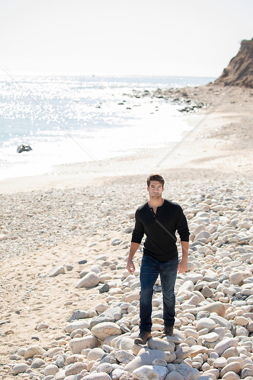 hot man walking on a rocky beach