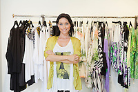 Portrait of a happy mid adult woman with arms crossed in front of clothes rack