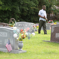Clarence Partlow walks the rows of headtsones at Plantersville Cemetery in search of veterans buried there.