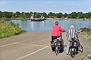 Nederland, Afferden, 27-8-2014De pont over de Maas tussen de dorpen, rivierdorpen, Afferden in Limburg en Vortum Mullum bij Boxmeer in Noord-Brabant. Twee fietsers staan op de veerstoep te wachten.FOTO: FLIP FRANSSEN/ HOLLANDSE HOOGTE