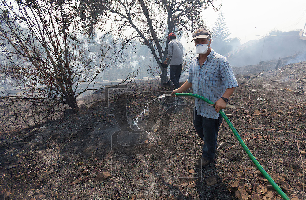 Portugal, Funchal, Madeira : A man extinguishes smoldering ashes in Camacha, Santa Cruz, near Funchal, on July 19, 2012. Massive fires broke out in Madeira island leading the evacuation of population in certain regions of the island. A contigent of firefighters plus a C-130 aircraft have been dispatched from mainland Portugal to help tackle the blazes. PHOTO / GREGORIO CUNHA