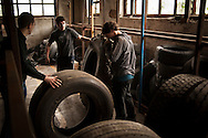 Some youg people move some tyres as they clean the old factory. Donostia (Basque Country). May 1, 2015.  A group of people occupies the former factory of Firestone, which was abandoned long ago, to promote alternative models of work, relationship and lifestyle initiatives. They will call it 'Eraldia' (Ocassion or opportunity in Basque language) (Gari Garaialde / BostokPhoto)