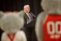 Ms and Mr Wuf listen as Chancellor Randy Woodson (center) introduces the Wolfpack's new athletic director at a press conference in Reynolds Coliseum.