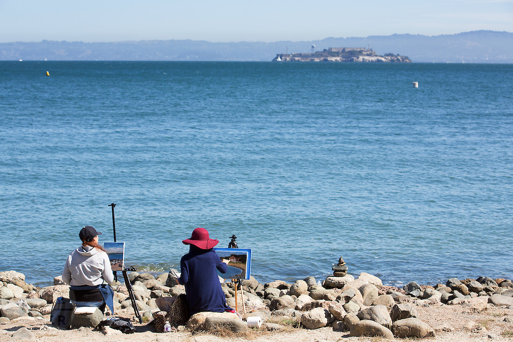 Twee vrouwen schilderen de baai van San Francisco met in de achtergrond Alcatraz. De Amerikaanse stad San Francisco aan de westkust is een van de grootste steden in Amerika en kenmerkt zich door de steile heuvels in de stad.<br /> <br /> Two women paint at San Francisco Bay with in the background Alcatraz. The US city of San Francisco on the west coast is one of the largest cities in America and is characterized by the steep hills in the city.