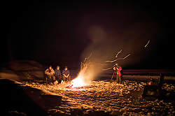 A photographer takes a picture of people sitting around a warm bonfire at night in the arctic circle, at Bettles, Alaska.