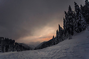 Mountain hill covered in snow at gloomy sunrise