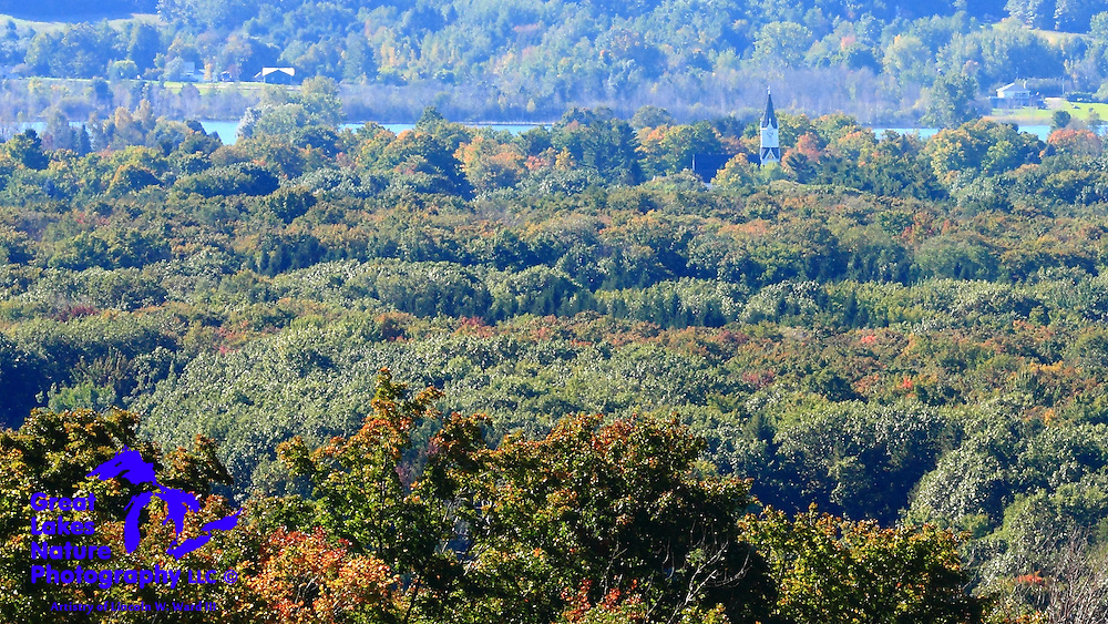 This is an extreme telephoto shot that I took of Arcadia Michigan. The distance between the trees in the foreground and the houses in the background is perhaps 10 miles. The photo was taken from the Benzie Scenic Turnout on M-22. It's a great place to stop on your Michigan tour (both the town and the turnout). The turnout, also known as the Arcadia Overlook, or even Inspiration Point, might be the best vantage point over Lake Michigan, anywhere.