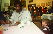 A curious young girl looks at the musician, Jazzy B during a Mayor's Christmas lights event in Brixton town hall in December 1989, London England.