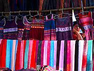 Woman peeping through fabrics at North Vietnam market