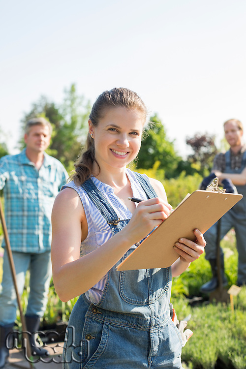 Portrait of beautiful supervisor holding clipboard with gardeners standing in background at plant nursery