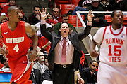 Utah head coach Jim Boylen, center, yells out instructions to his team during an NCAA college basketball game, Wednesday, Jan. 19, 2011, in Salt Lake City. Also in the photo is New Mexico forward Chad Adams (4) and Utah guard Josh Watkins (15). (AP Photo/Colin E Braley)