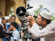 17 JUNE 2015 - YAHA, YALA, THAILAND:   An Imam uses a telescope to look for the crescent moon to mark the beginning of Ramadan in Yaha District of Yala province. Thousands of people came to Yaha District in Yala province of Thailand for the Hilal - the first sighting of the crescent moon that marks the official beginning of the Muslim holy month of Ramadan. Despite cloudy weather and intermittent rain showers, the moon was sighted and religious leaders declared the official beginning of Ramadan.   PHOTO BY JACK KURTZ