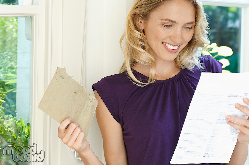 Woman looking at letter looking happy