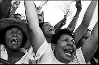 Unidentified women sing revolutionary hymns during the celebration of May Day in the Revolution square in Havana, Cuba on May 1st, 2003. By subtly influencing people's moods and appealing to their sense of patriotism, after more than four decades, communist government in Cuba still counts with the support of the majority. (Photo/Cristobal Herrera)