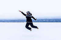 Photographer Lola does her signature jump pose on a frozen lake in Lahti, Finland.
