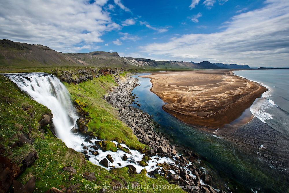 Red sand and waterfall in Snaefellsnes west Iceland