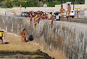 HAVANA, CUBA - OCTOBER 21, 2006: Unidentified people sunbathe at the Malecon seawall in Havana, Cuba.