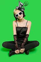 Beautiful young woman wearing sunglasses and headgear while sitting with legs crossed over green background