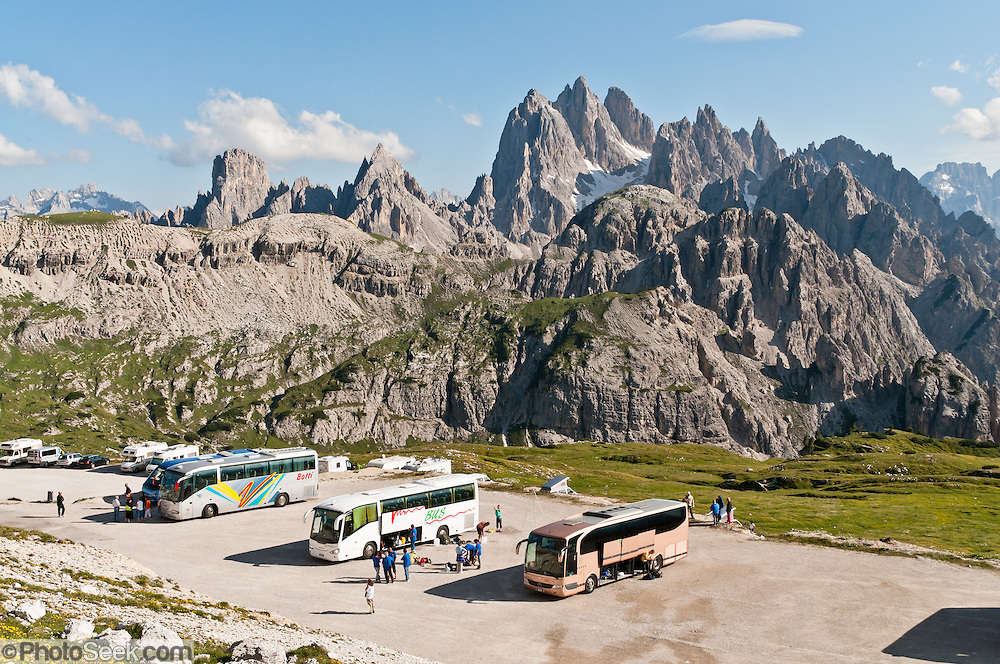 """At Rifugio Auronzo bus parking lot, the peaks of the Cadini Group jut high in the Dolomites range near Cortina d'Ampezzo, Veneto region, Italy, Europe. In the Cadini di Misurina, Cima Grande rises to 2999 meters (9839 feet), between Cima Piccola 2857 m (9373 ft) and Cima Ovest or """"Western Peak"""" 2973 m (9754 ft). Hike for spectacular views around Tre Cime di Lavaredo (Italian for """"Three Peaks of Lavaredo,"""" or in German called Drei Zinnen, """"Three Merlons""""). The Dolomites are part of the Southern Limestone Alps, in northern Italy, Europe. UNESCO honored the Dolomites as a natural World Heritage Site in 2009."""