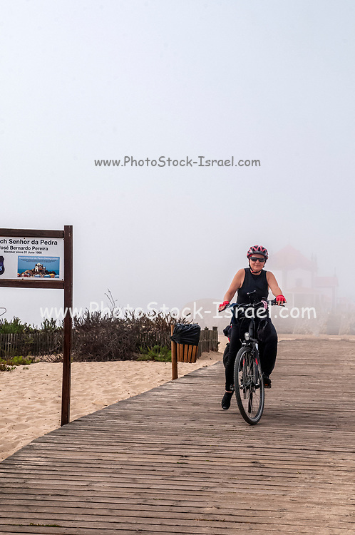 woman cycles on the Eurovelo 1 Atlantic coast route Near Porto, Portugal. The Atlantic Ocean coast on the left