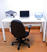 Empty office chair with laptop on desk