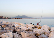 A man fishes in the Bay of Naples along the Mergellina with Mt. Vesuvius in the background.