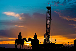 Two cowboys on horseback in front of an oil and gas drilling rig in the Eagle Ford Shale play at sunset in South Texas.