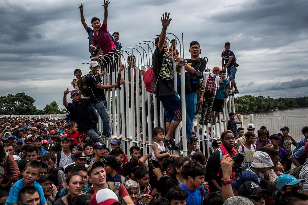 Migrantes se aglomeran alrededor y encima de las rejas abiertas de la aduana mexicana, en el puente fronterizo entre Guatemala y México, para acceder a suelo mexicano. Tecún Umán, Guatemala. 19/10/2018<br /> <br /> A mediados de octubre 2018, miles de migrantes hondureños abandonaron sus casas para emprender el viaje hasta los Estados Unidos, recorriendo casi 5.000 kilómetros hasta la ciudad fronteriza de Tijuana en menos de dos meses.<br /> Las 10.000 personas (según estimaciones de la UNCHR) que conformaron la caravana visibilizaron el fenómeno migratorio por primera vez en Centroamérica, denunciando las problemáticas de extrema pobreza y violencia presentes en los lugares de origen.