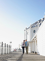 Couple holding hands walking along pier