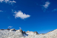 Blu sky, clouds, and the mountains (Dragontail Peak) in the upper Enchantments, Enchantment Lakes Wilderness Area, Washington Cascades, USA.