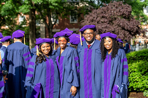 A group of graduating Howard University students smiling for a group photo in the main yard.