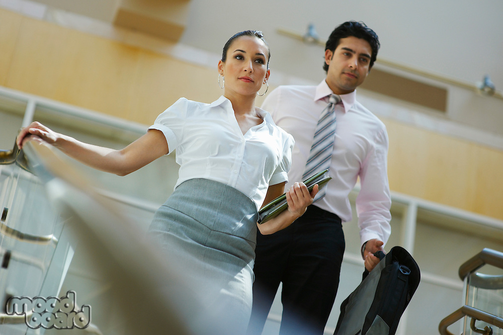Young business woman and business man walking down stairs