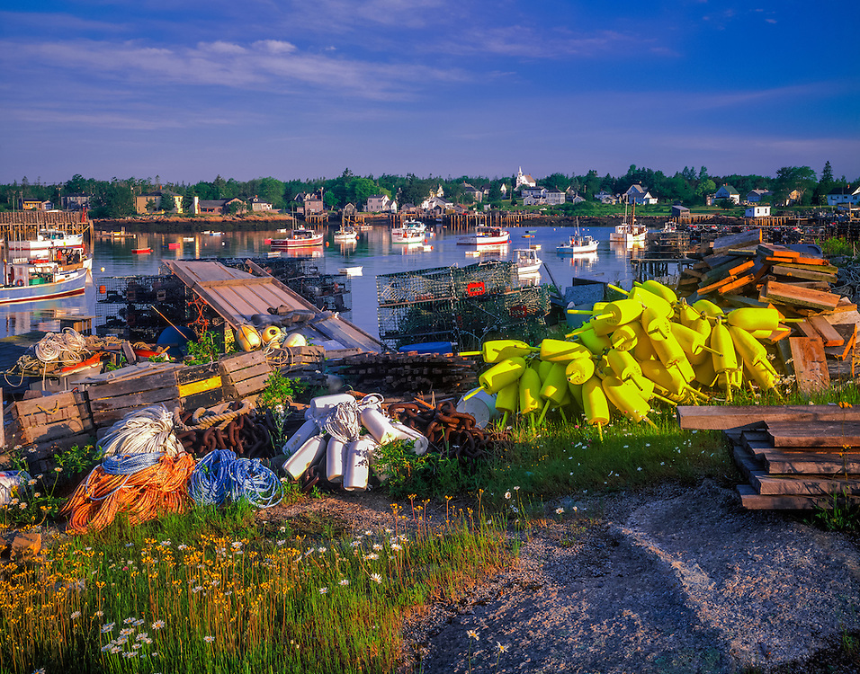 Lobster fishing gear piled on shore, harbor with boats beyond, Corea, ME