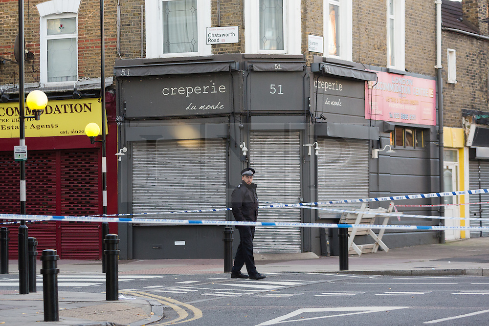 © Licensed to London News Pictures. 27/09/2015. London, UK. A police officer at the cordon on Chatsworth Road. Police have launched a murder investigation after a man was shot dead in the street outside Regal Pharmacy next to Mighty Meats butcher shop in Chatsworth Road, Hackney, east London yesterday. Photo credit : Vickie Flores/LNP