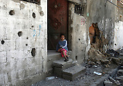 ..A young Palestinian girl sits on the doorstep of her home which was heavily damaged my IDF artillery fire in Beit Hanoun in northern Gaza November 9,2006. Eighteen people, many of which were women and children were killed in their sleep in the attack.