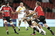 JOHANNESBURG, SOUTH AFRICA - 23 April 2011: Isaac Ross of the Chiefs drives with the ball with Patric Cilliers and a fellow player of the Lions tackling during the Super Rugby Match between the MTN Lions and the Chiefs held at Coca Cola Park Stadium, Johannesburg, South Africa. Photo by Dominic Barnardt