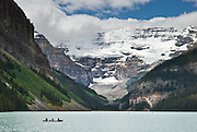 A family of four canoes in the blue-green waters of Lake Louise beneath glacier clad Mount Victoria (3459 meters/11350 feet), Banff National Park, Alberta, Canada. This is part of the big Canadian Rocky Mountain Parks World Heritage Site declared by UNESCO in 1984.