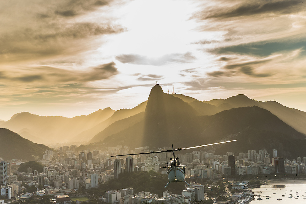 The city of Rio de Janeiro at sunset with on the background Christo redentor and a helikopter on the foreground, Rio de Janeiro, Brazil.
