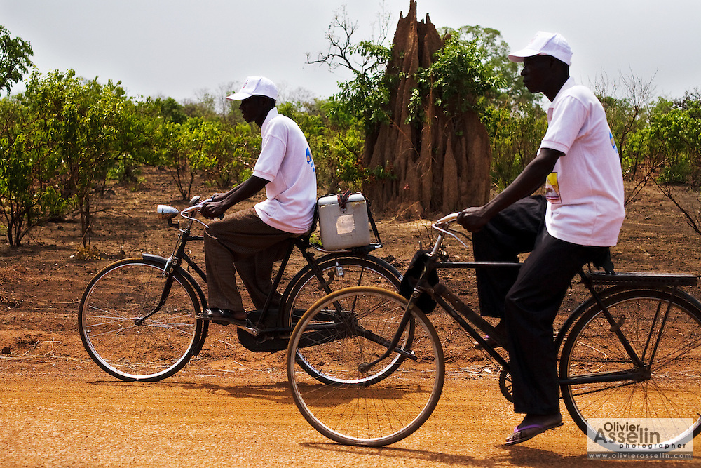 Health workers ride bicycles along a dirt road outside Makango, northern Ghana, as they head to villages to vaccinate children during a national polio immunization exercise on Tuesday March 31, 2009.