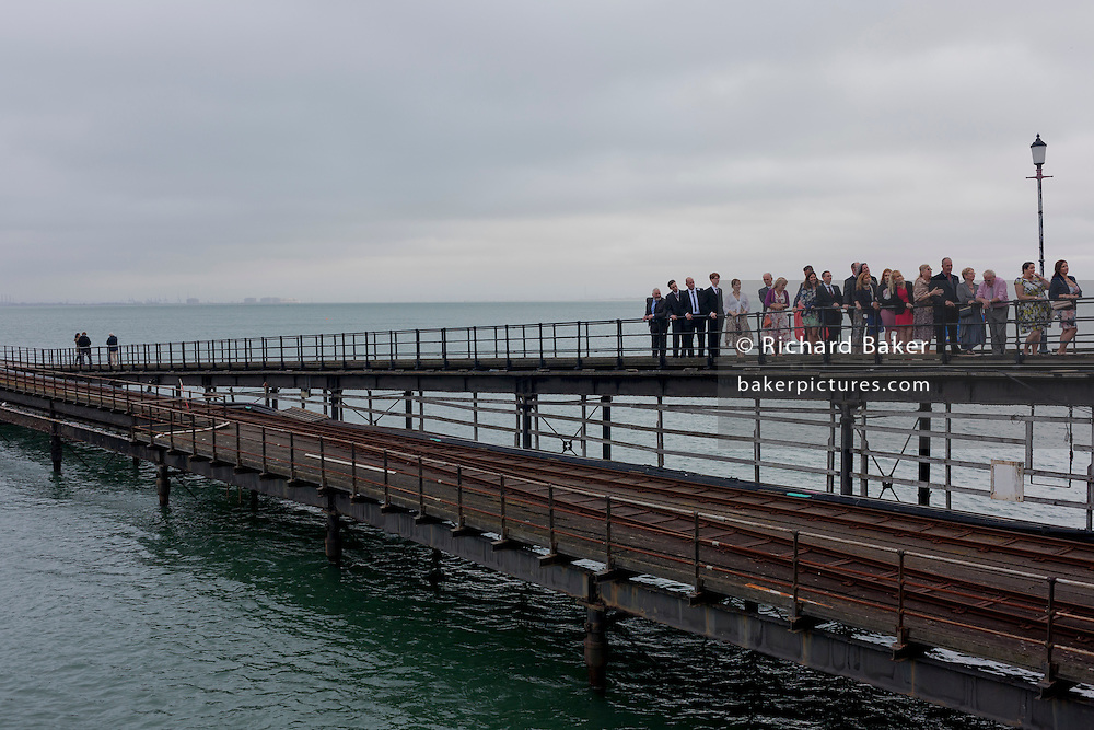 A wedding group stand on a grey day on Southend Pier, the world's longest at a mile and a quarter, at Southend-on-Sea, Essex.