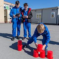 Daniel Kolesnikov and Harry Kennedy watch Michael Anistenkov complete his task