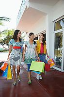 Three teenage girls (16-17) carrying shopping bags walking on street