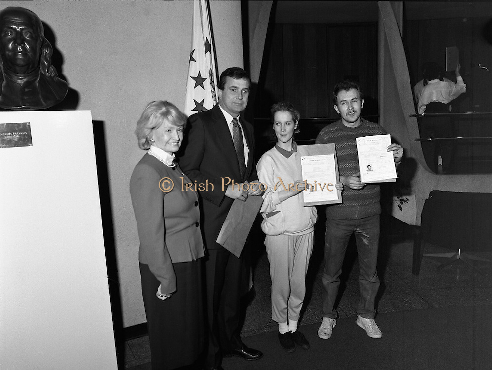Presentation Of Donnelly Visas.  (R71)..1988..19.01.1988..01.19.1988..19th January 1988..As part of his interest in Ireland Congressman Brian Donnelly promoted a visa scheme to easily allow Irish people entry into America. Known now as the Donnelly Visas,Congressman Donnelly came to The American Embassy in Dublin to present the new visas to those where lucky enough in the first draw to obtain the visas...Picture shows Congressman Donnelly presenting the new visa to two lucky recipients in the American Embassy in Dublin,Ambassador Heckler is also included in the picture.